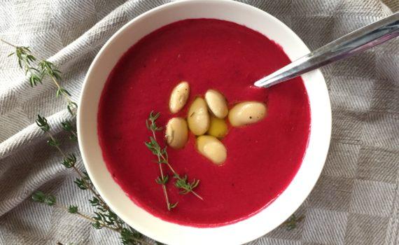 lautasella punaista keittoa, jonka päällä valkoisia papuja ja timjamia