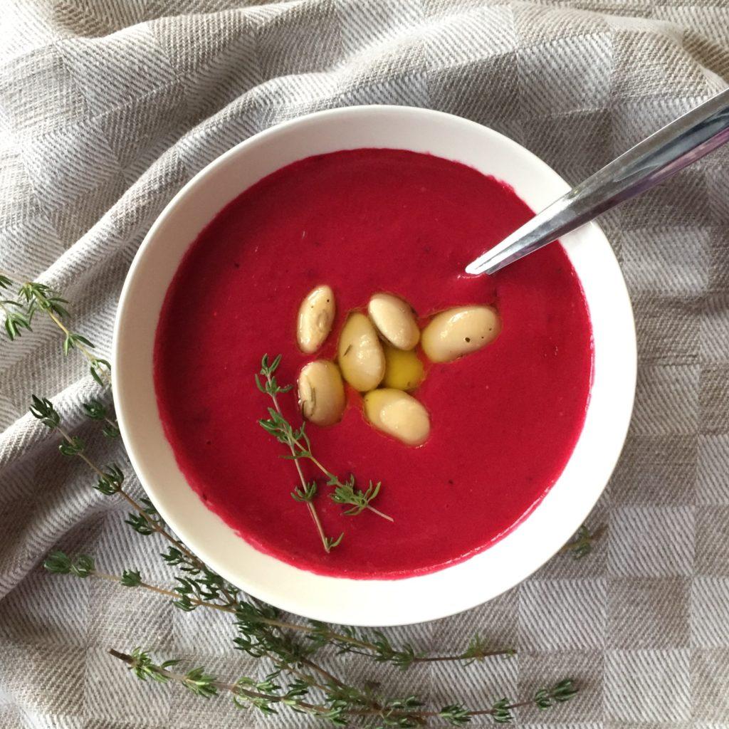 lautasella punaista keittoa, jonka päällä valkoisia papuja